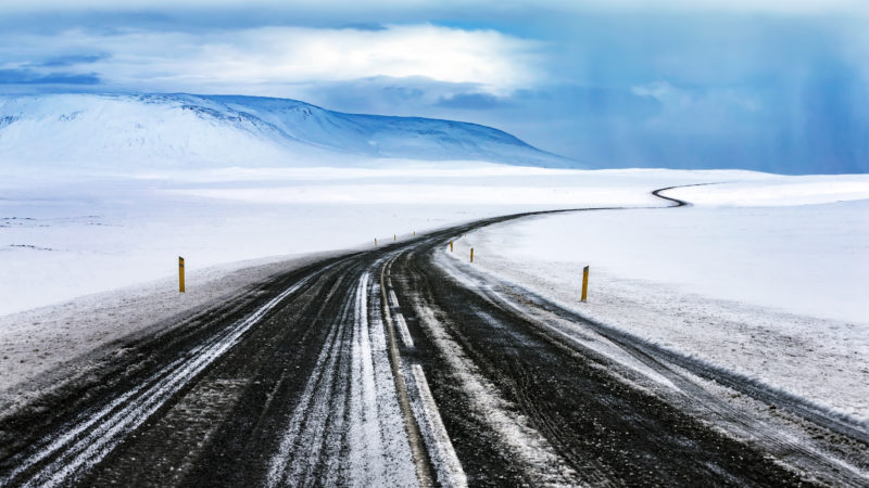 Positive travel Iceland Guide Snowy road, long curved highway among beautiful white snowy landscape, winter travel, beautiful nature of Iceland
