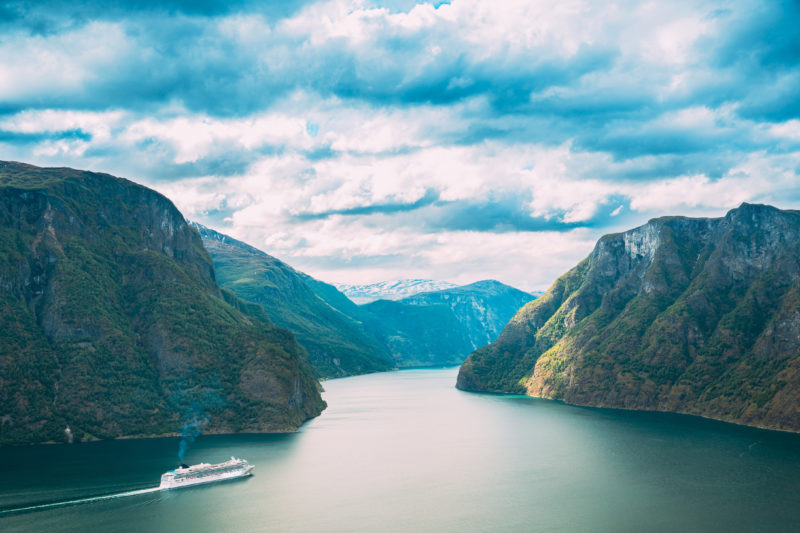 Positive Travel Iceland Guide Tourist Ship Ferry Boat Liner Floating In Amazing Fjord Sogn Og Fjordane. Summer Scenic View Of Famous Natural Attraction Landmark And Popular Destination In Summer.