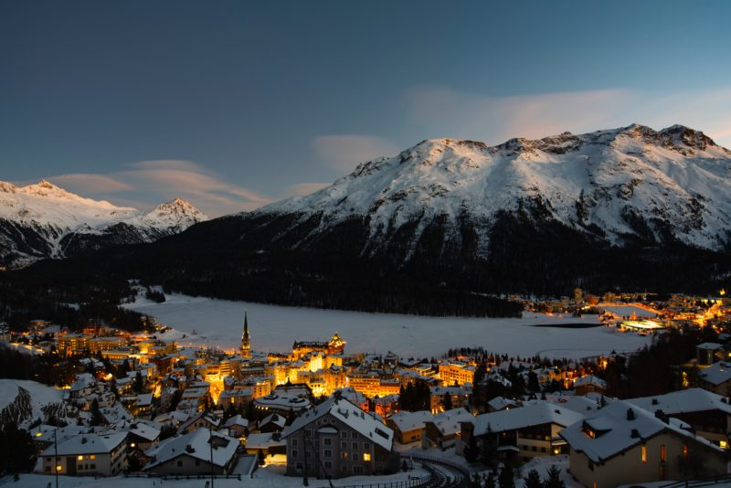 Positive Travel Best Sustainable Ski Resorts in Switzerland St Moritz snow covered village and frozen lake view at sunset