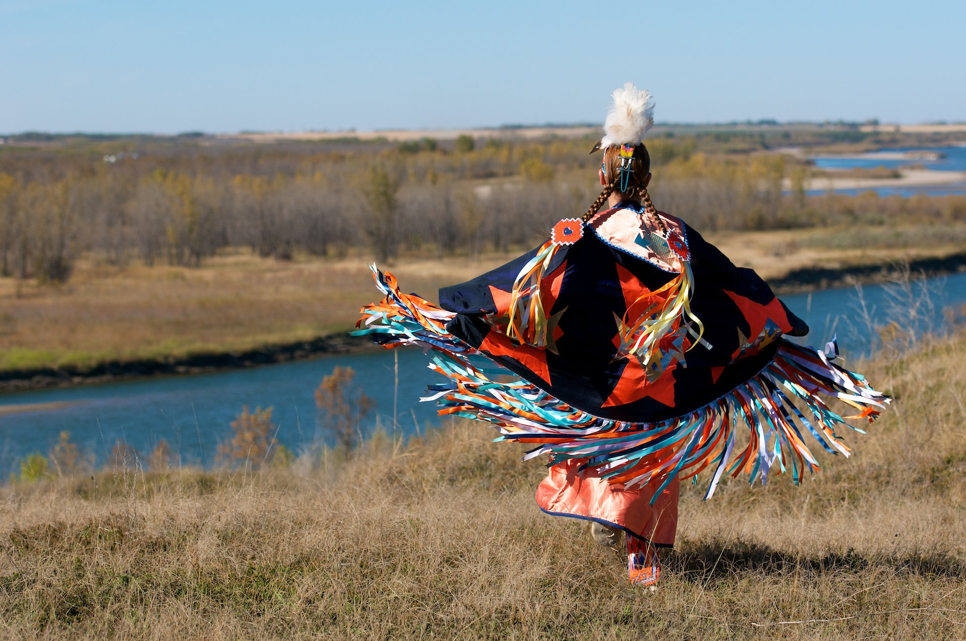 woman First Nations fancy shawl dance in a field alongside the river