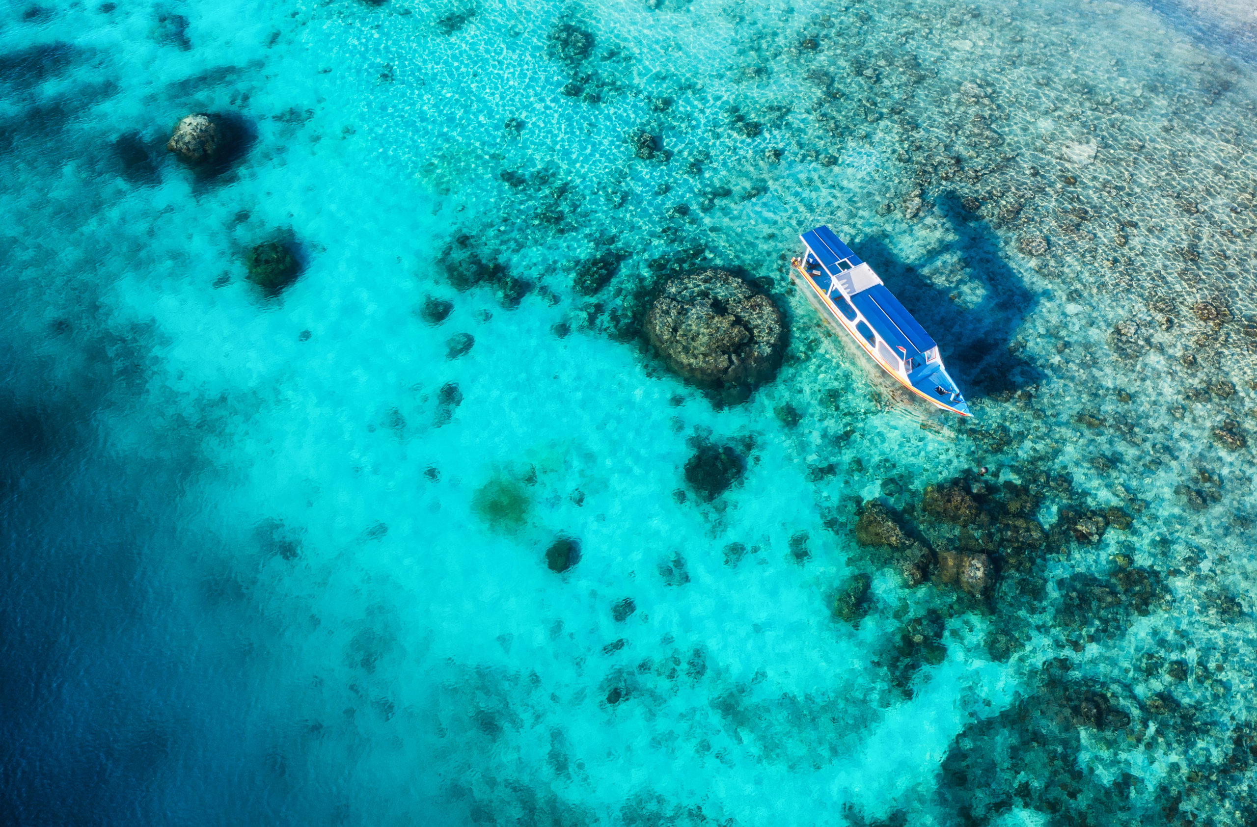 Boats on the water surface and beach from top view. Azure water background from drone. Summer seascape from air. Travel - image